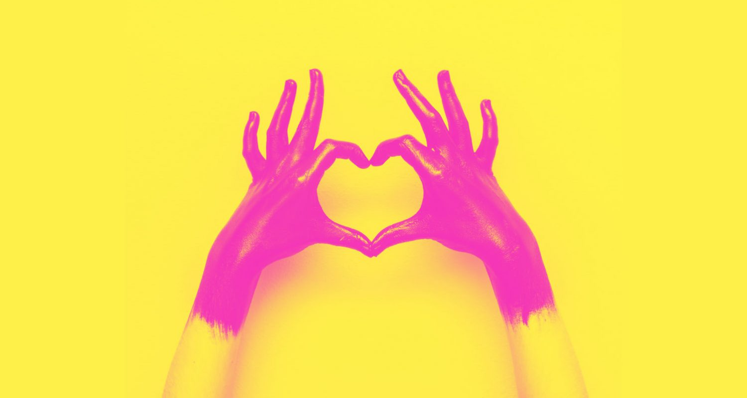 hands in black paint send heart. love and minimal fashion concept. yellow and pink double color effect