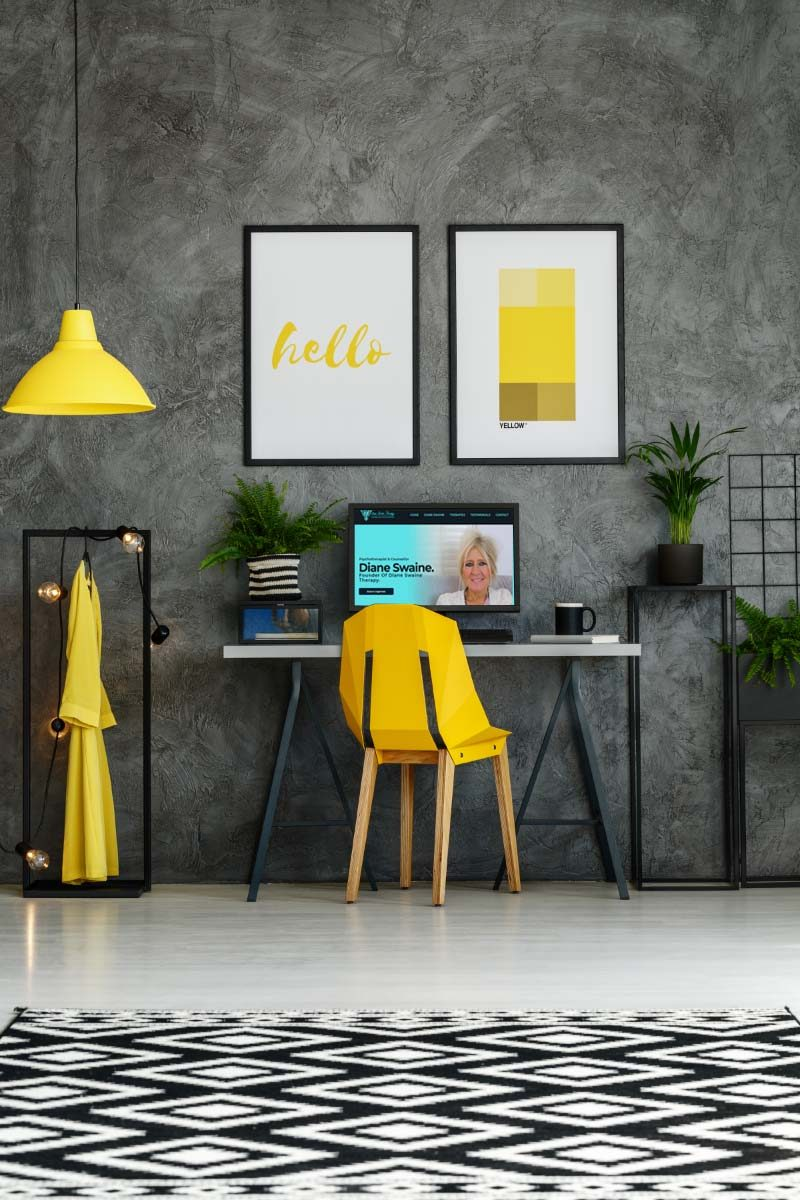 Room with metal desk, yellow accents, textured wall, mock-up posters